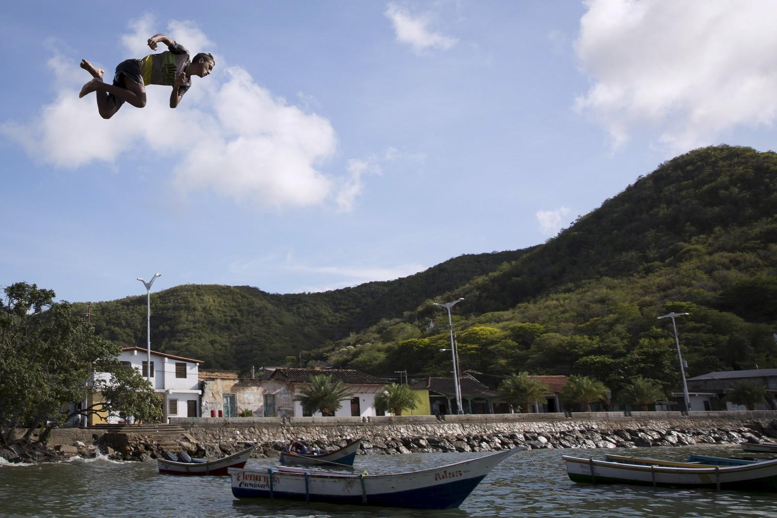 Denne gutten hopper i det i Rio Caribe, Venezuela.
