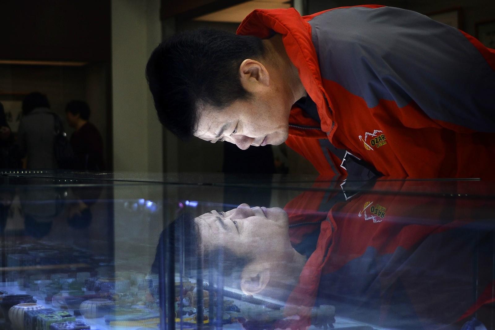 En mann titter på seg selv og antikviteter i Beijing i Kina.