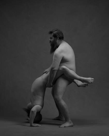 En naken mann står i bro med låra rundt hoftene på en naken mann med skjegg