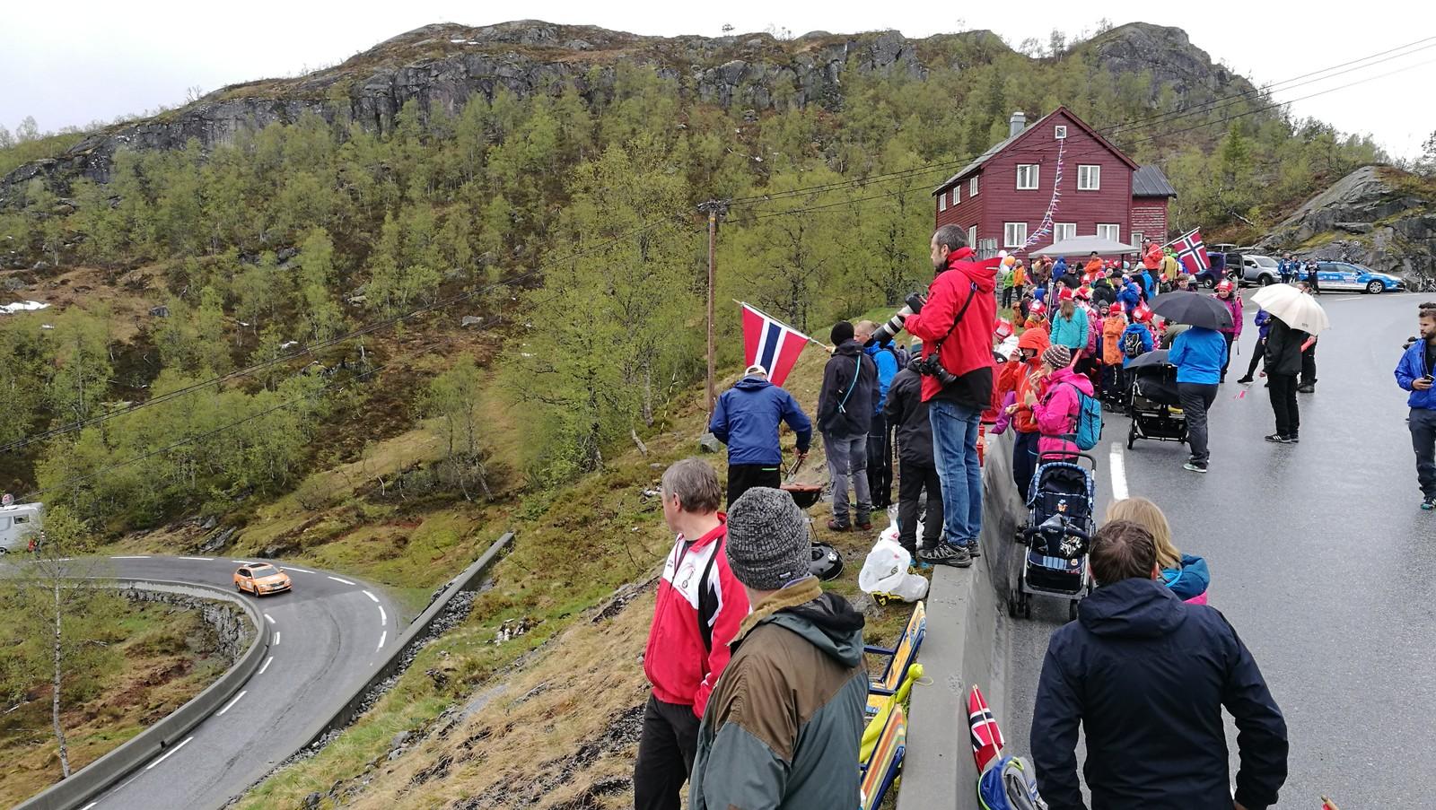 Folk har stilt seg opp på toppen av Røyrvikfjellet for å ta imot syklistane.