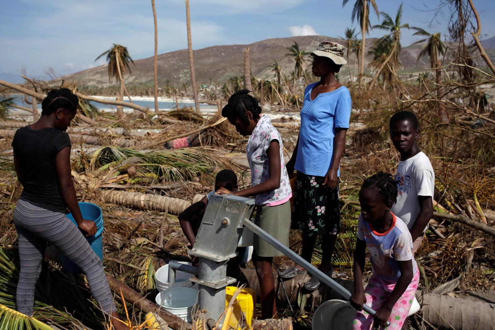Folk samler vann ved en vannpumpe etter i Coteaux, på Haiti, søndag.