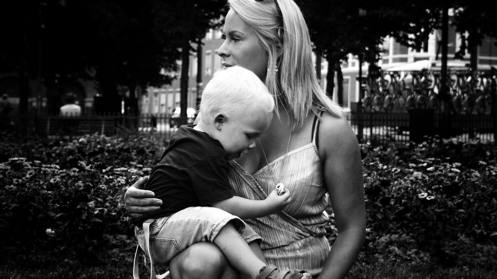 Sorthvitt bilde av en ung kvinne med barnet sitt i fanget. Kvinnen er i profil og ser mot venstre. Barnet er en lyslugget liten gutt som leker med morens halskjede. Begge har sommerklær på seg og de er i en park med blomster i bakgrunnen.