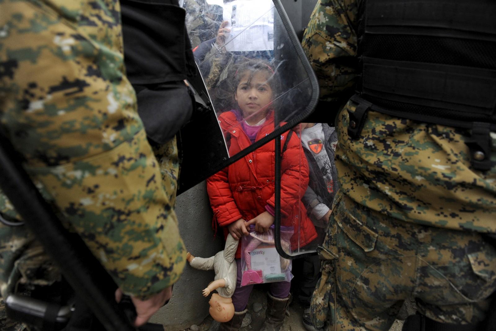En jente på flukt holder fast på dukkene sine mens to makedonske politimenn sperrer veien ved grensa mellom Hellas og Makedonia.