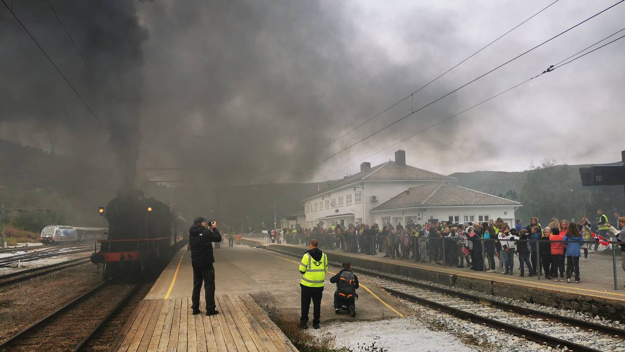 Røyken ligger tjukt på Dombås stasjon da damptoget forlater stasjonen.