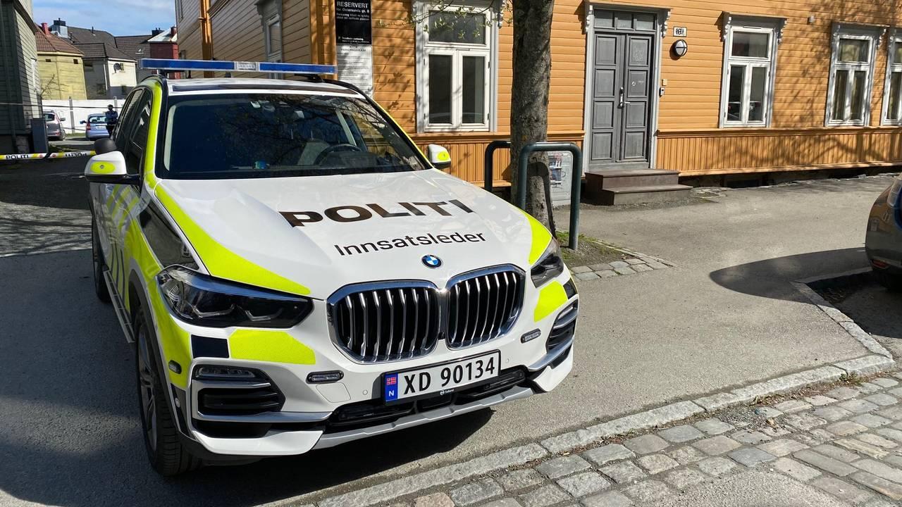 En politibil står parkert i gata hvor politiet nå etterforsker drap i Trondheim. I bakgrunnen ser vi en gul bygård.