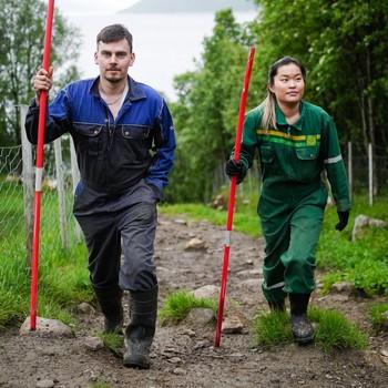 Ann-Hilde Albertsen og Christian Ottesen går med hver sin røde brøytestikker oppover en ujevn natursti på Reinøya.