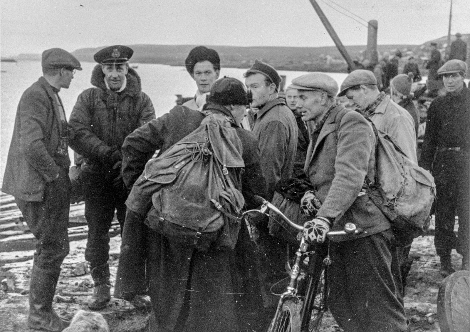 Original bildetekst: En av de første novemberdager i år ankom fra Storbritannia til Nord-Norge en norsk militærdelegasjon under ledelse av oberst A.D. Dahl. Samtidig fulgte norske styrker som var utdannet i United Kingdom.  Ved ankomsten til Vadsø var den del av befolkningen som var blitt tilbake, møtt frem på bryggen.