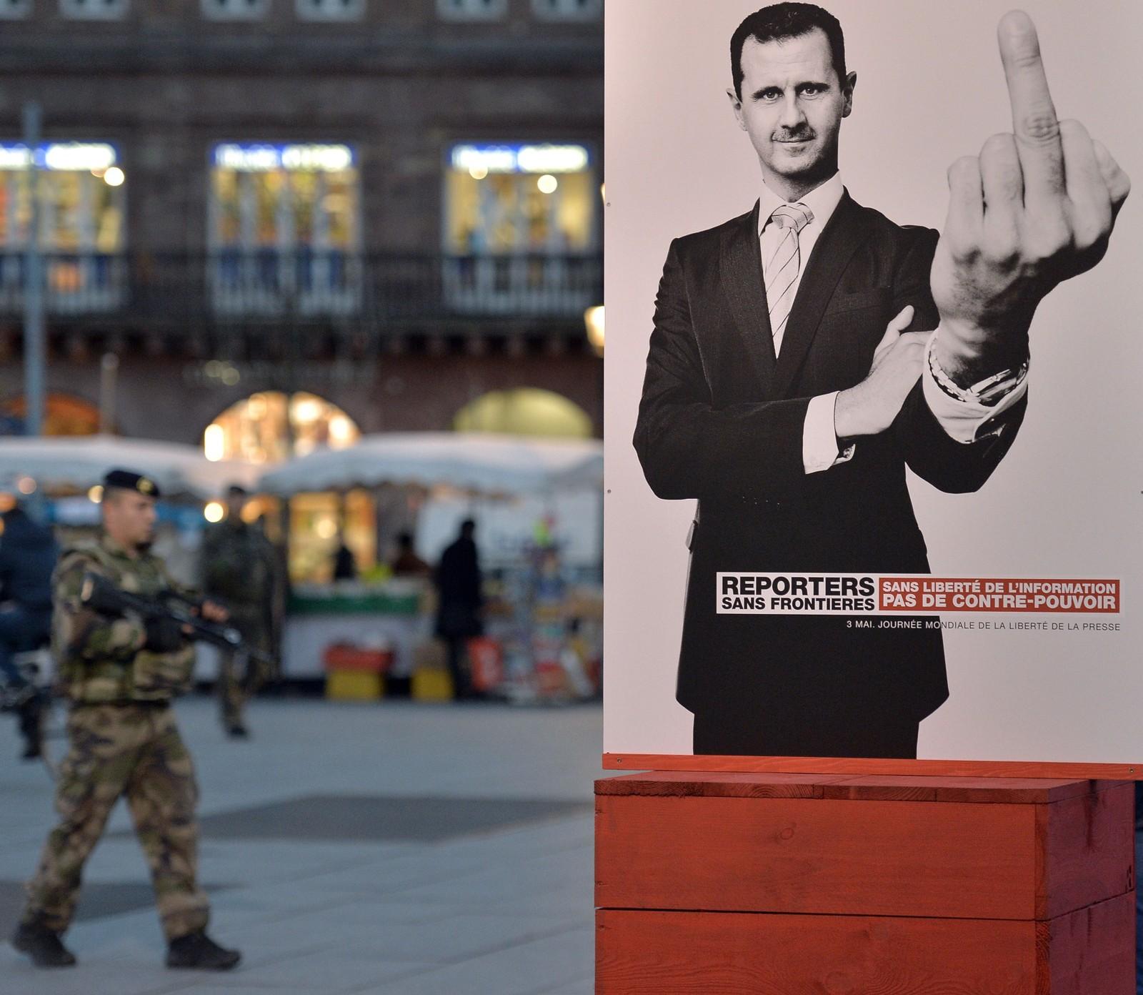 En fransk soldat passerer en plakat av Syrias president Bashar al-Assad få dager etter terrorhandlingene i Paris. Plakatene er signert organisasjonen Reporters sans frontières (reportere uten grenser), og viser 39 ulike motiver av statsledere de anser som fiender av ytringsfriheten.