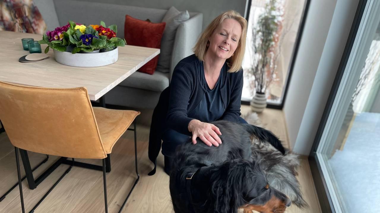 Unni Sandøy sitter på huk på gulvet og klapper hunden sin.