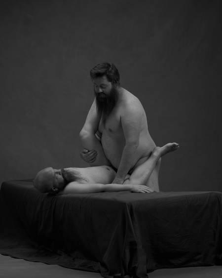 En naken mann med skjegg ligger på ryggen med bena opp langs brystet til en annen naken mann