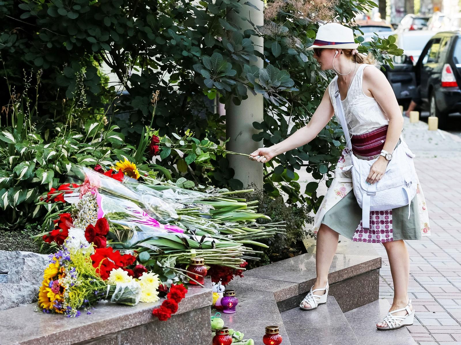 En kvinne legger ned roser til minne om ofrene for terroren i Nice, foran den franske ambassaden i Kiev i Ukraina.