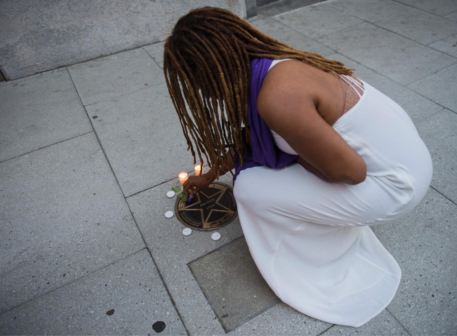 En kvinne tenner lys for å minnes Prince. Her utenfor Warnerteatret i Washington, DC.