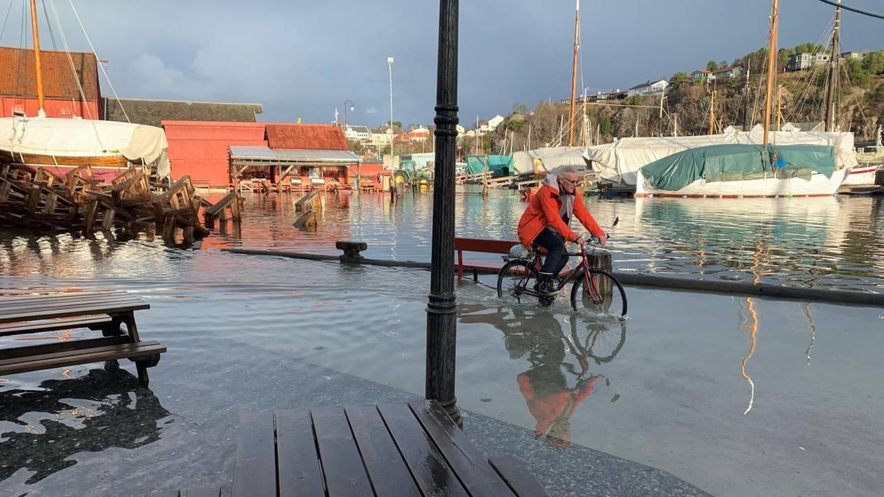 En mann sykler med vann langt oppover sykkelhjulene i Ålesund sentrum.