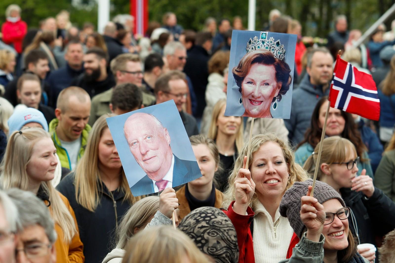 Publikum med plakater av kong Harald og dronning Sonja på Slottsplassen i anledning kongeparets 80-årsfeiring.