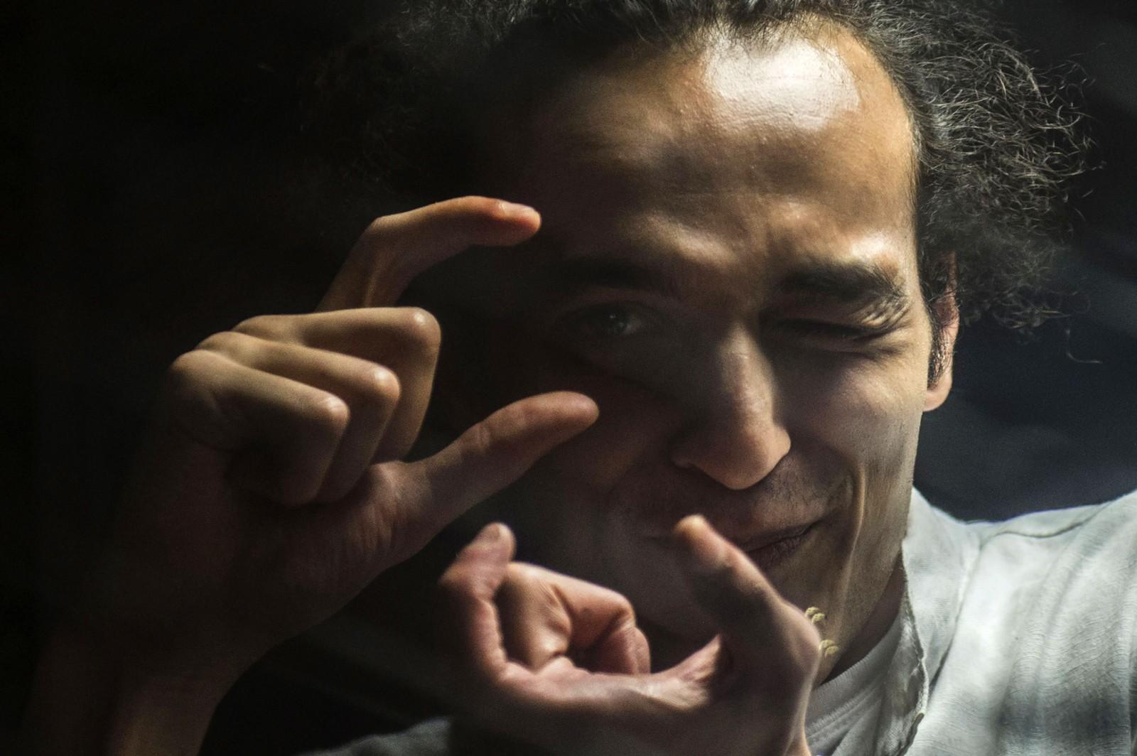 Den egyptiske fotografen Mahmoud Abdel Shakour, kjent som Shawkan, tar et bilde med et usynlig kamera i Kairo den 9. august. Han står i et glassbur mens han venter på at rettssaken mot han skal starte. Han har sittet i fengsel i tre år etter at han tok bilder av politiet da de ryddet en islamistisk demonstrasjonsleir. Flere utenlandske journalister ble også arrestert, men de er sluppet fri. Shawkan risikerer nå dødsstraff. Han har tidligere tatt bilder for BBC, Time, Die Zeit og Bild.