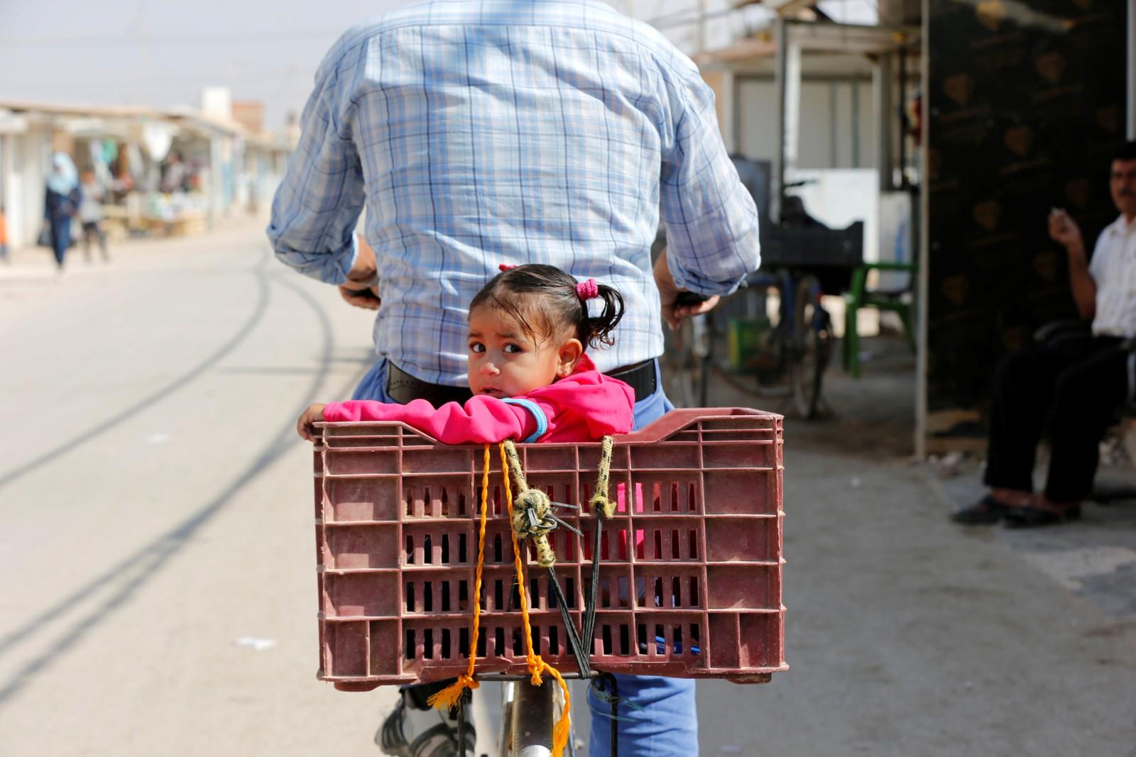 En syrisk flyktning sykler med datteren til markedet i Al-Zaatri-flyktningleiren ved byen Mafraq i Jordan 17. september.