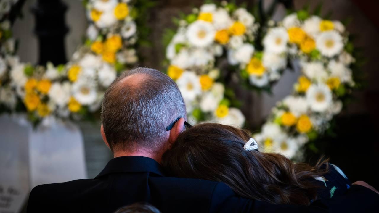 Foreldrene til Cecilie lener hodene inntil hverandre. I bakgrunnen er de gule blomstene