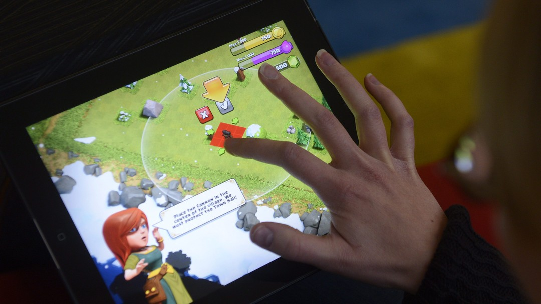 A woman plays the Clash of Clans game of Finnish computer game maker Supercell on a tablet computer on December 14, 2012 in Helsinki. Finnish computer game maker Supercell has sold control of the company for 1.1-billion-euro ($1.5 billion) to two Japanese investors, SoftBank and GungHo, the Helsinki-based company announced on its website on October 15, 2013. AFP PHOTO / Lehtikuva/VESA MOILANEN FINLAND OUT