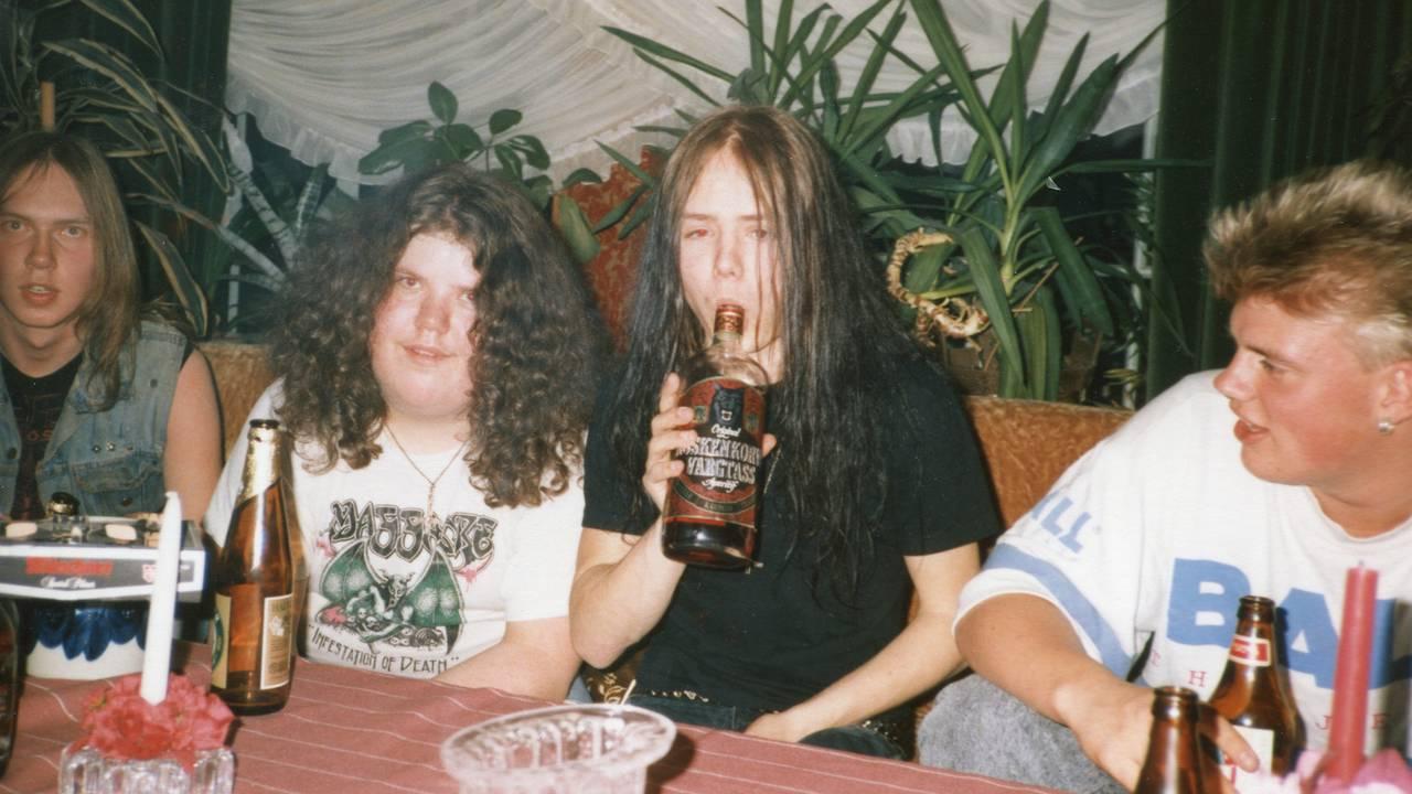 Jon «Metallion» Kristiansen og Øystein Aarseth som ungdom på fest. Øystein sitter med en flaske brennevin i hendene som han ser ut til å drikke fra.