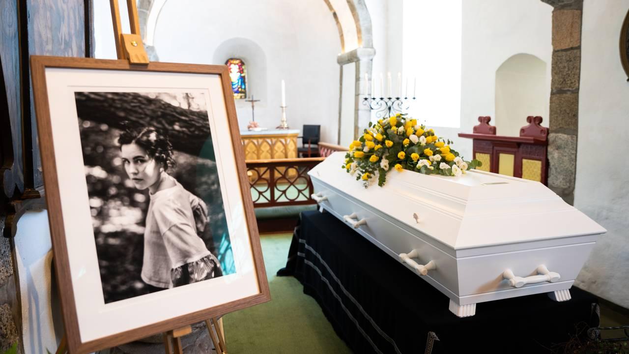 Bilde av Cecilie ved siden av en hvit kiste med masse gule blomster
