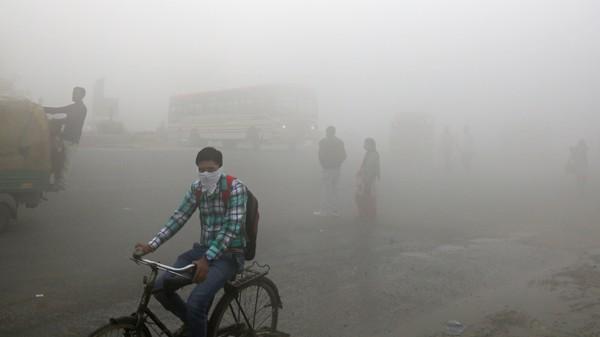 En mann på sykkel dekker ansiktet i den tykke smogen i New Delhi i India.