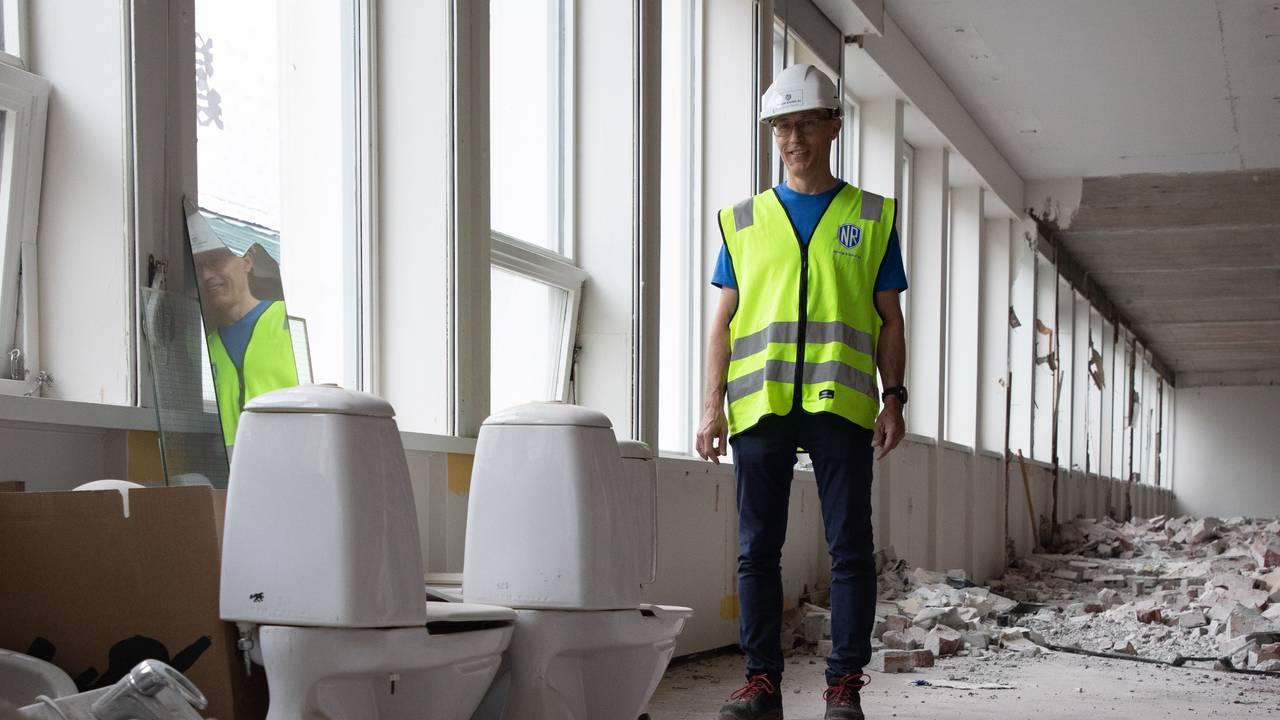 Svein Egil Dagsland står midt i et stort rom. På gulvet ligger det store hauger med ødelagt teglsten. Til venstre står det to brukte toaletter og en pappeske og et speil. Dagslyset skinner inn fra vinduene.