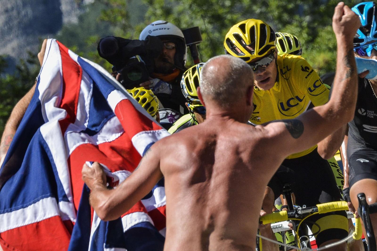Chris Froome i den gule trøya måtte tåle nærkontakt med en rekke tilskuere. Han ble spyttet på minst to ganger, og ble kastet urin på. I dette tilfellet går det bra med Sky-rytteren. AFP PHOTO / JEFF PACHOUD