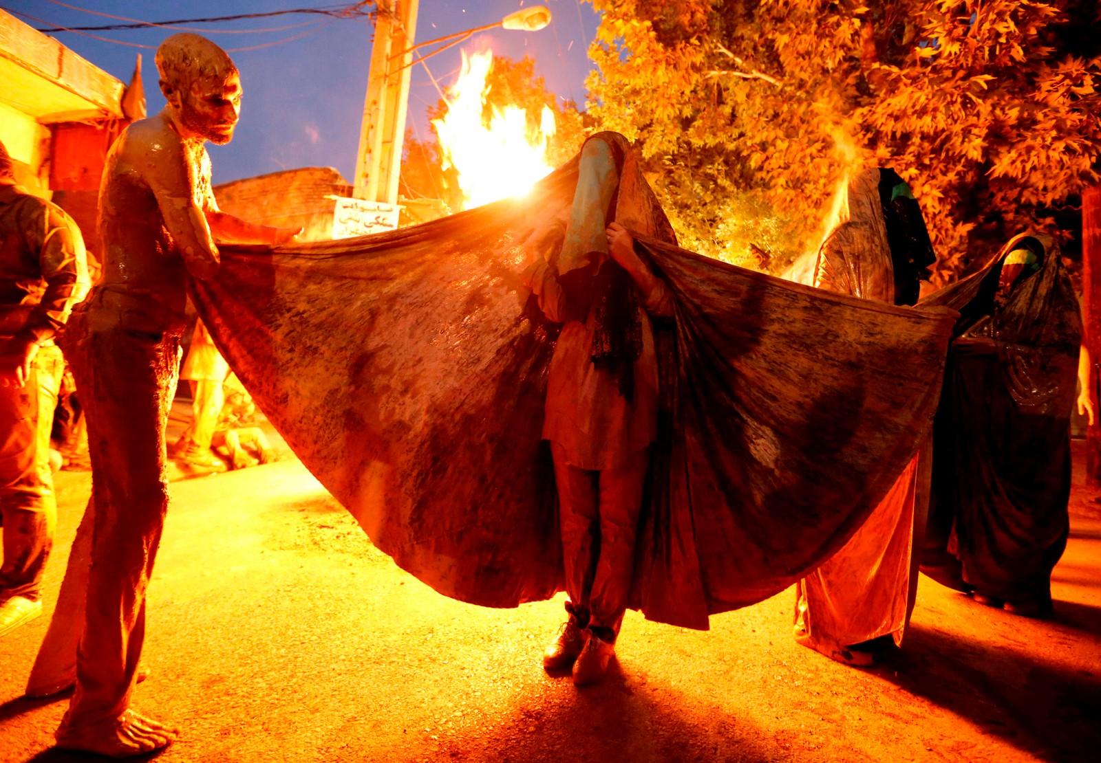 Iranske shia-muslimer gnir kroppen inn i gjørme og samles rundt et bål i Khorramabad. Ritualet utgjør en del av 'Kharrah Mali'-feiringa.