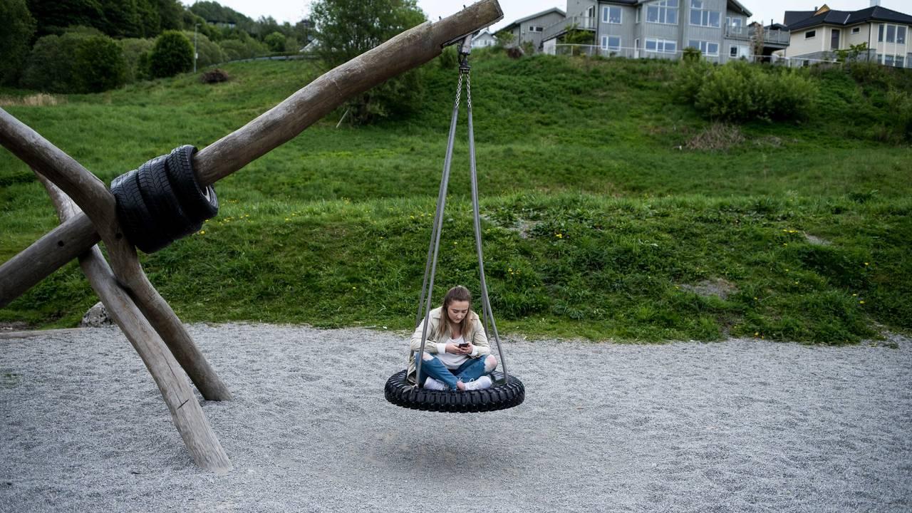 Bilde av Ingebjørg som sitter på en huske laget av et slags gummihjul. Husken er festet i et trestokk.