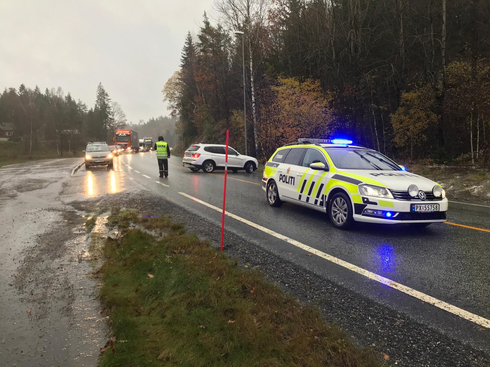 Politiet dirigerer personbiler forbi overvann på gang/sykkelsti i Tvedestrand. Tunge kjøretøy må vente til omkjøring er på plass.