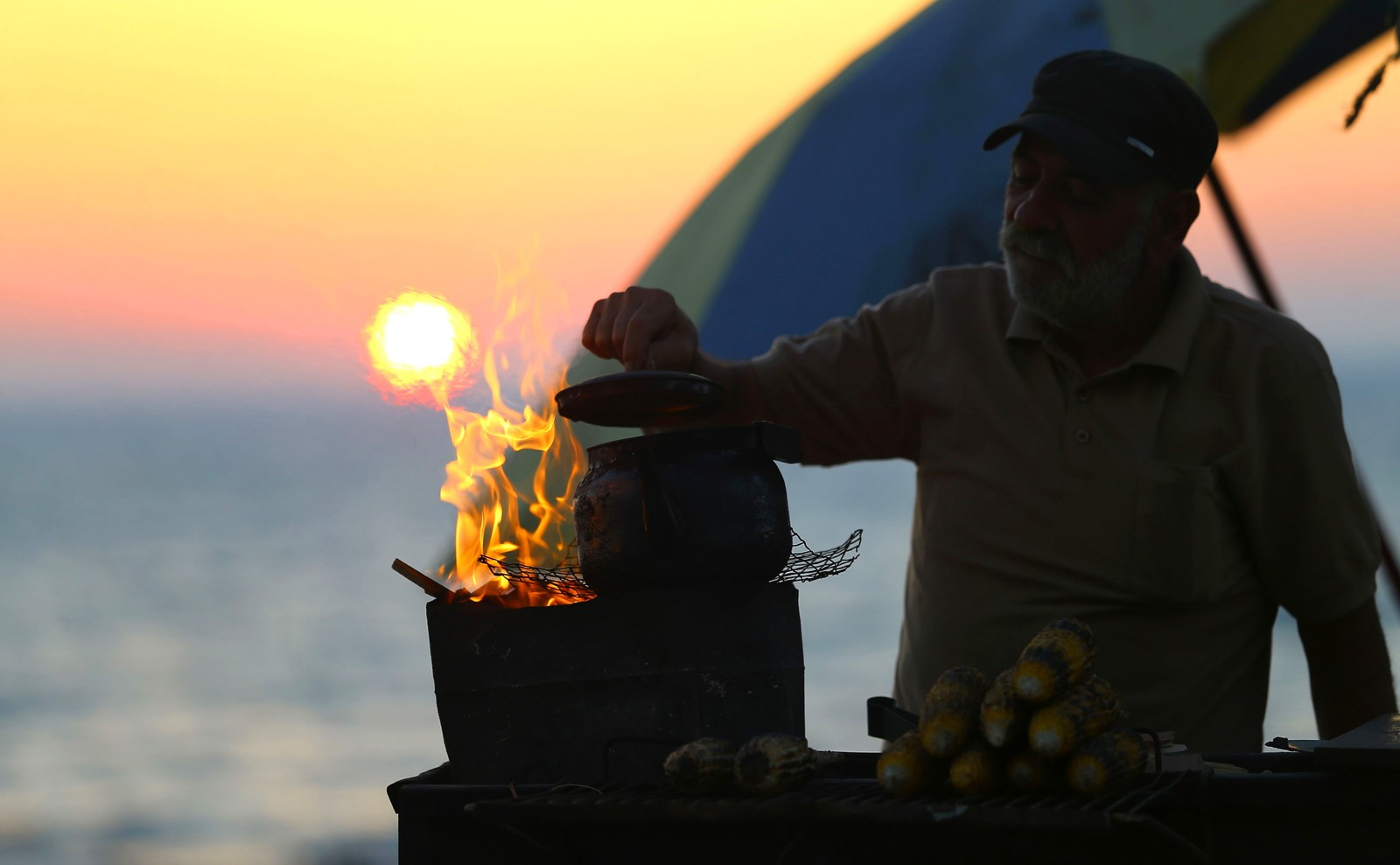 Det er på tide med en kopp te etter en lang dag med maisgrilling ved en strand i Gaza.