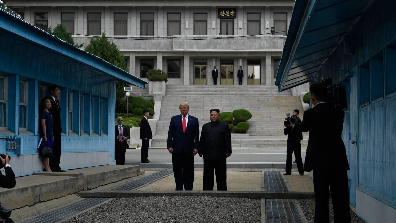 Donald Trump og Kim Jong-un stående på den nordkoreanske side av grensen, på vei tilbake til sør