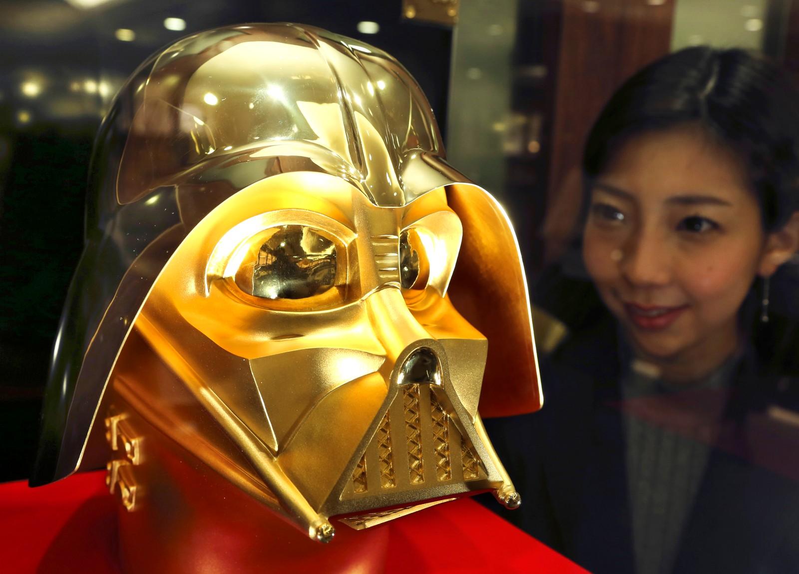 En kvinne som er ansatt i gullsmedforretningen Ginza Tanaka i Tokyo ser på en Darth Vader-maske laget av 24 karat gull. Masken veier 15 kilo og koster nesten 12 millioner kroner. Masken er laget for å markere at det er 40 år siden den første Star Wars-filmen kom.