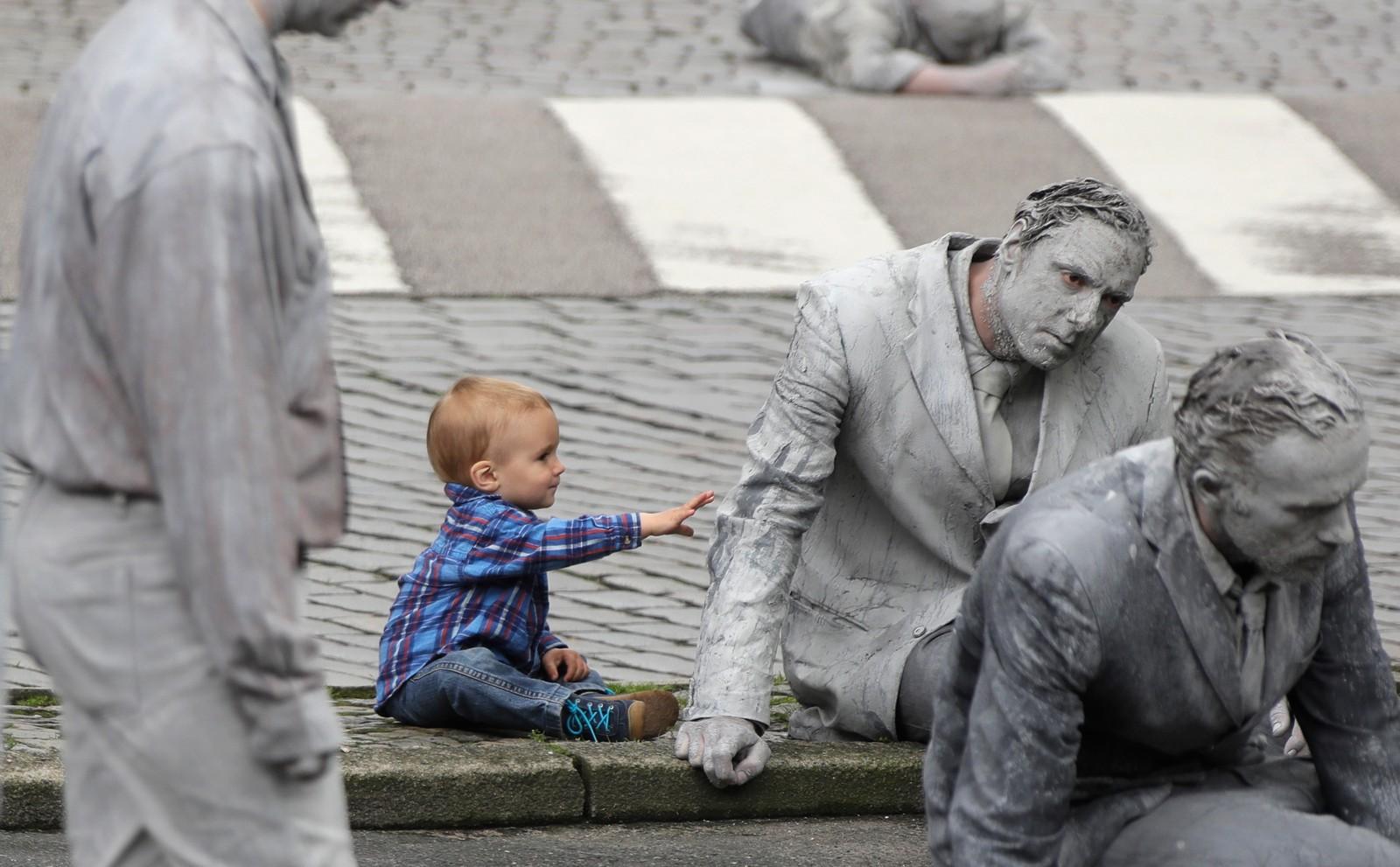 """En liten gutt prøver, kanskje litt spent, å ta på en av deltagerne i performance-verket """"1000 gestalten"""" (1000 former). De utøvende bevegde seg stille og sakte gjennom Hamburgs gater i protest mot G20-møtet onsdag denne uka."""