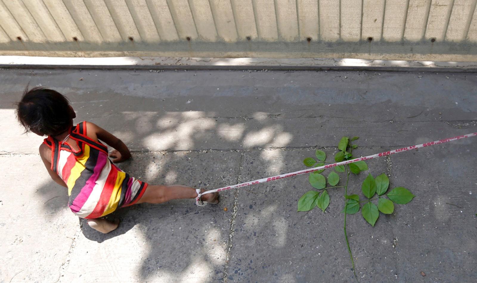 Sarta Kalara fortalte denne uka til Reuters at hun ikke har noe annet valg enn å binde fast dattera Shivani (15 mnd.) på bygningsplasen der hun og mannen arbeider. Kalara forklarte at hun gjør det for at datteras egen sikkerhet. De tjener rundt 31 kroner dagen hver ved å grave ned kabler i den indiske byen Ahmedamad. Den lille jentas bror er tre og et halvt år. Gammel nok til ikke å bli bundet fast, men for ung til å passe lillesøstera.