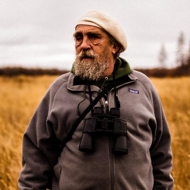 Sergey Zimov står i en gulnet eng.