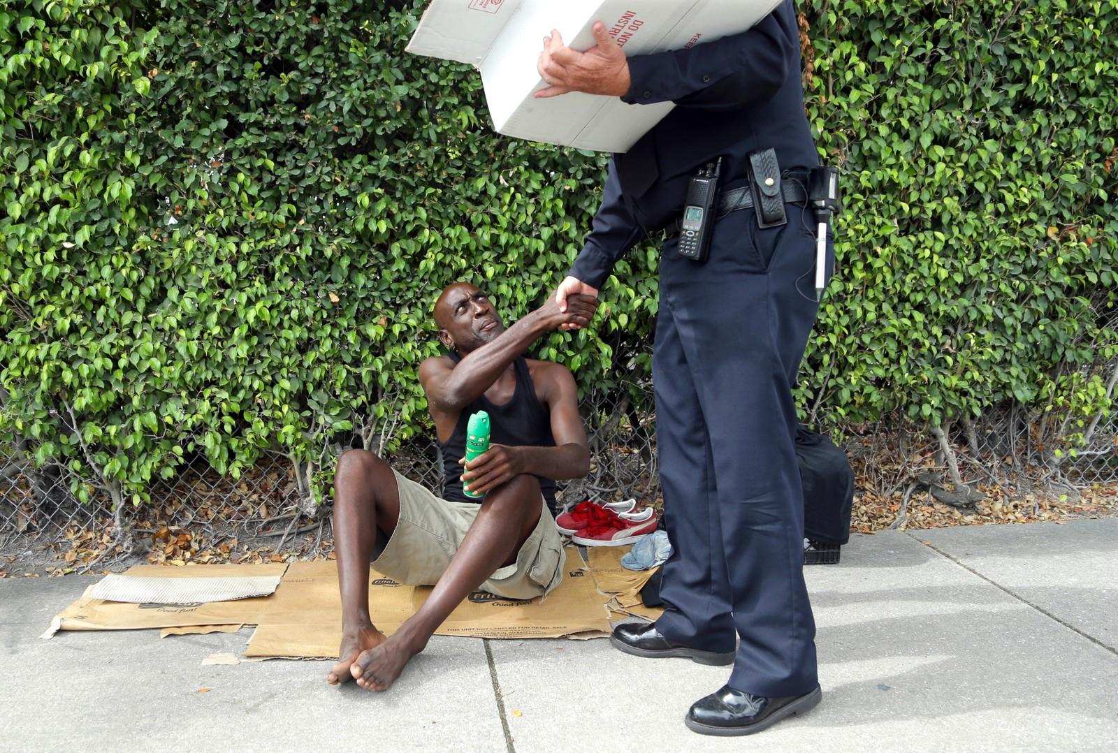 45 år gamle Lorenzo Ward, som er hjemløs, takker politimannen James Bernat etter å ha fått en sprayflaske med insektmiddel i nabolaget Wynwood i Miami i USA. Myndighetene ber gravide kvinner om å unngå dette området fordi det skal være mygg der som kan smitte mennesker med zikaviruset. Bildet er tatt 2. august. Politimannen delte ut 50 flasker denne dagen.