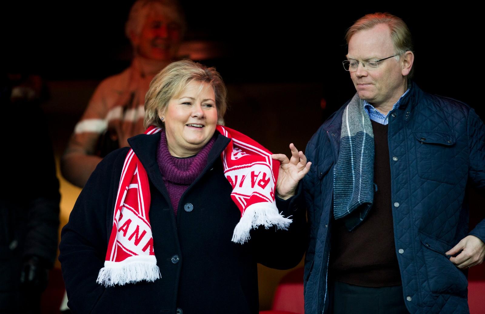 Statsminister Erna Solberg med Brann-skjerf og hennes mann Sindre Finnes på tribunen.