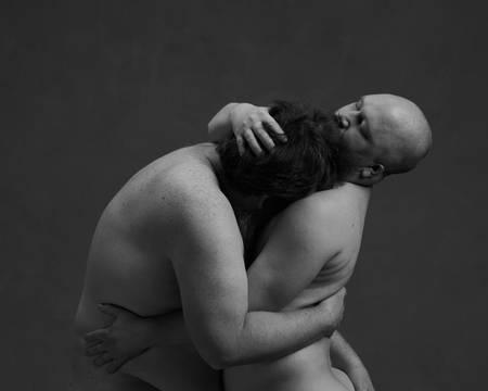 To nakne menn omfavner hverandre. De har øynene lukket og holder rundt hverandres overkropper.