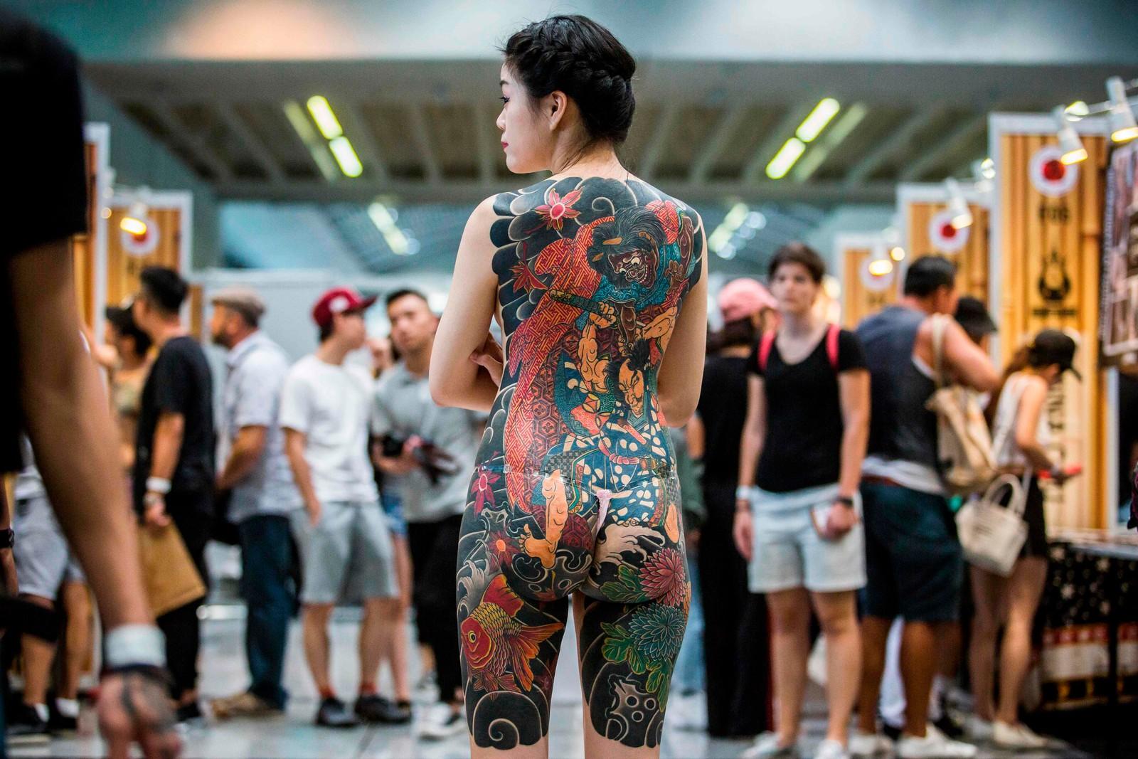 En kvinne viser fram tatoveringene sine for fotografen. Over 300 tatovører var samla til tatoveringsmesse i Hong Kong forrige helg.