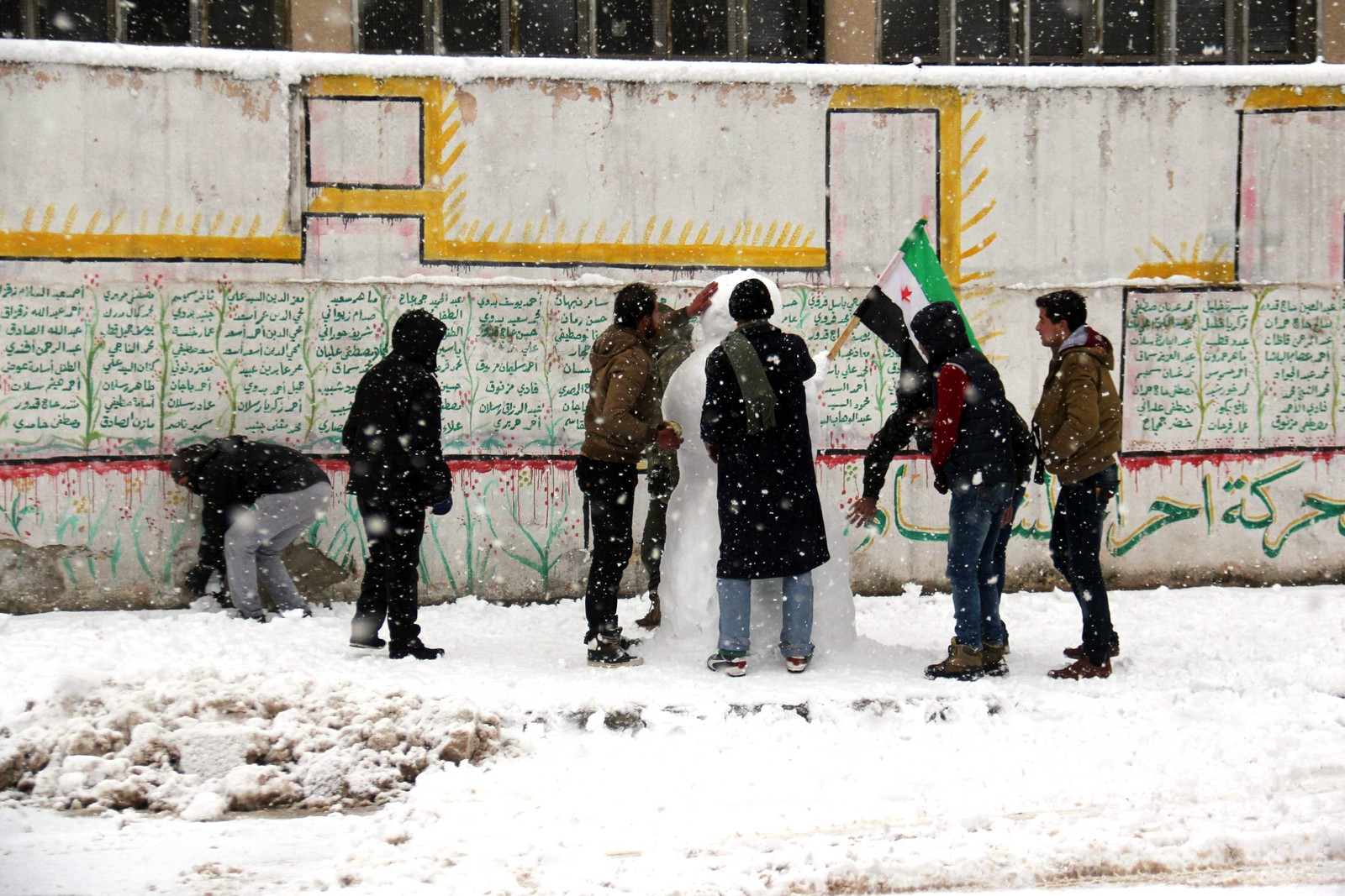Syrere bygger snømann i byen Binnish.