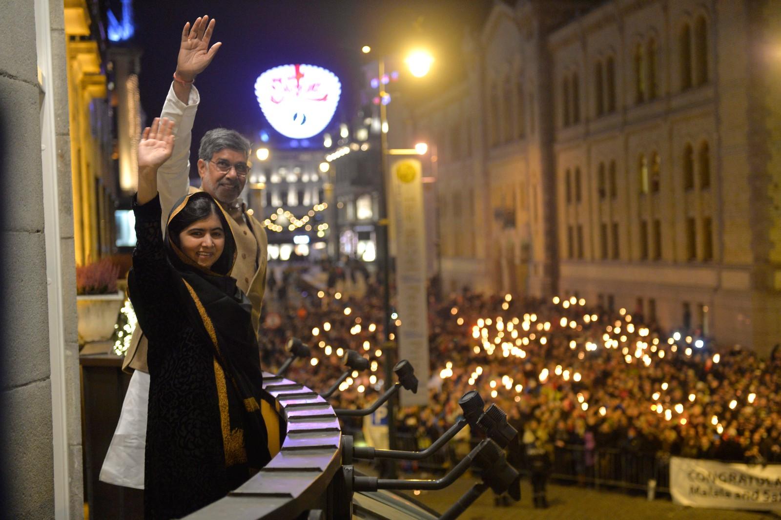 FAKKELTOG: Flere tusen mennesker deltok i fakkeltoget og sto utenfor Grand Hotel for å hylle Malala Yousafzai og Kailash Satyarthi. Nobels Fredspris 2014. Fredsprisvinnerne Kailash Satyarthi og Malala Yousafzai hilser fakkeltoget fra balkongen på Grand Hotel i Oslo onsdag kveld.  Foto: Fredrik Varfjell / NTB scanpix