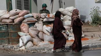 Kvinner passerer et militært sjekkpunkt i Homs