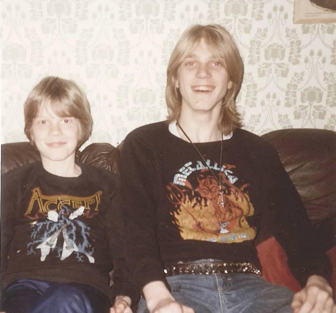 Bilde av Anders og Pelle Ohlin som ungdommer i en sofa. Begge har på seg hver sin metal-band-genser og ser ganske fornøyde ut.