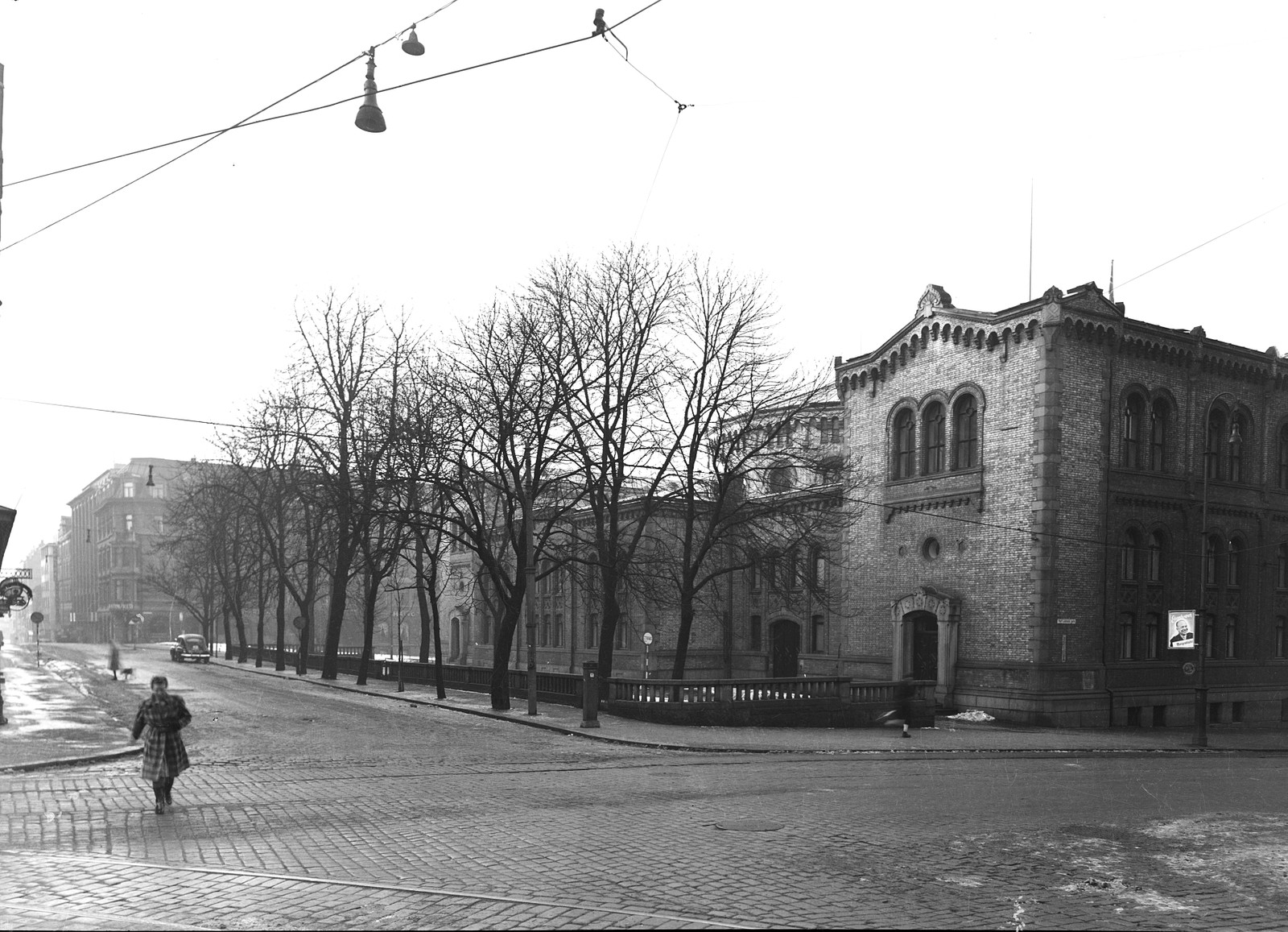 Stortingets bakside slik det opprinnelig så ut. Døren nærmest Karl Johans gate ble benyttet som daglig inngang fram til 1929. Riksarkivet holdt til i den lave bygningen ut mot Akersgata fram til 1914. Bygget ble revet i 1953 for å gi plass til et nytt kontorbygg. Foto: Ukjent / Stortingsarkivet / NTB scanpix