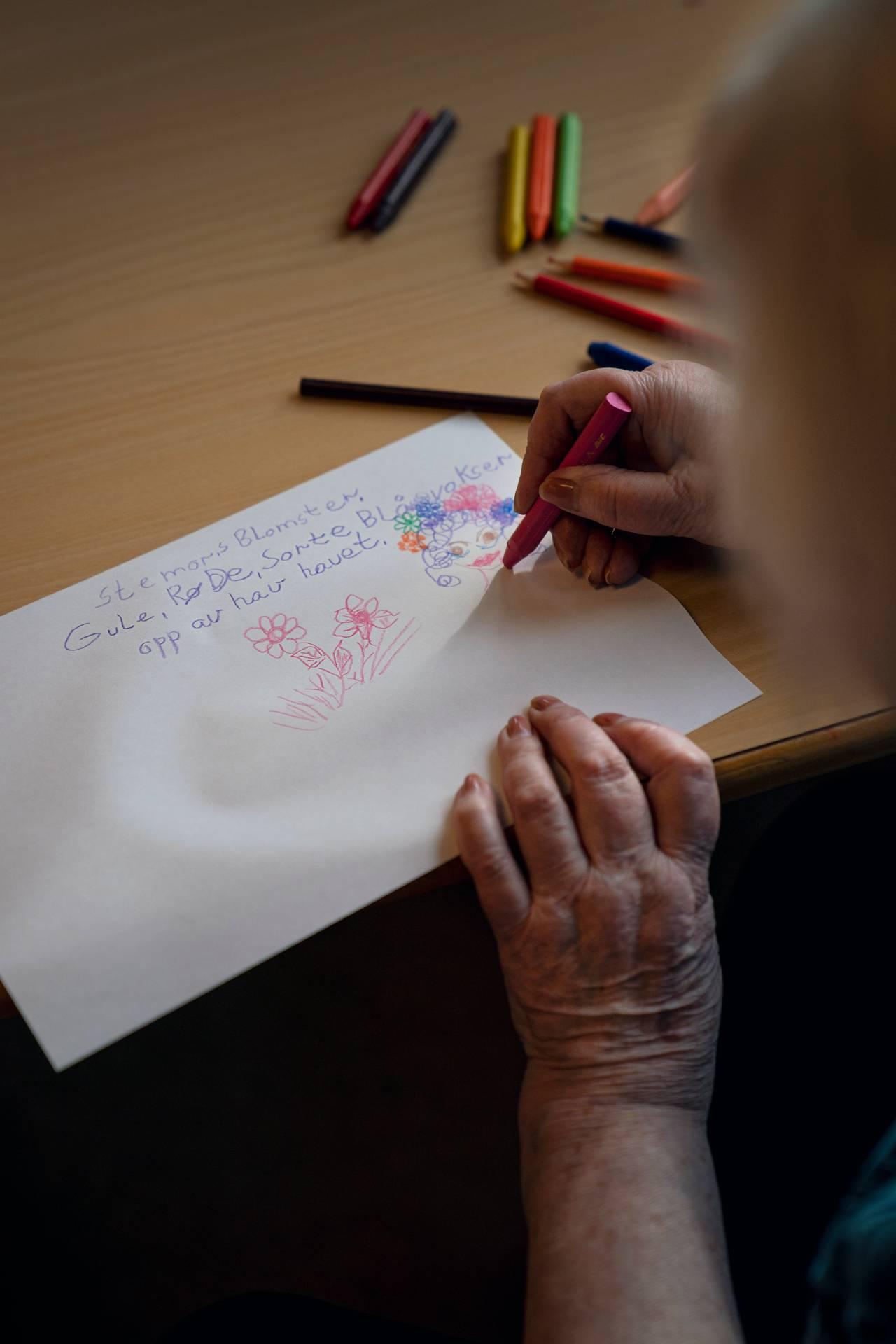 """Anne Marie tegner. På arket står diktet hun har skrevet med teksten """"Stemorsblomster, gule, røde, sorte, blå, vokser opp av havet"""""""