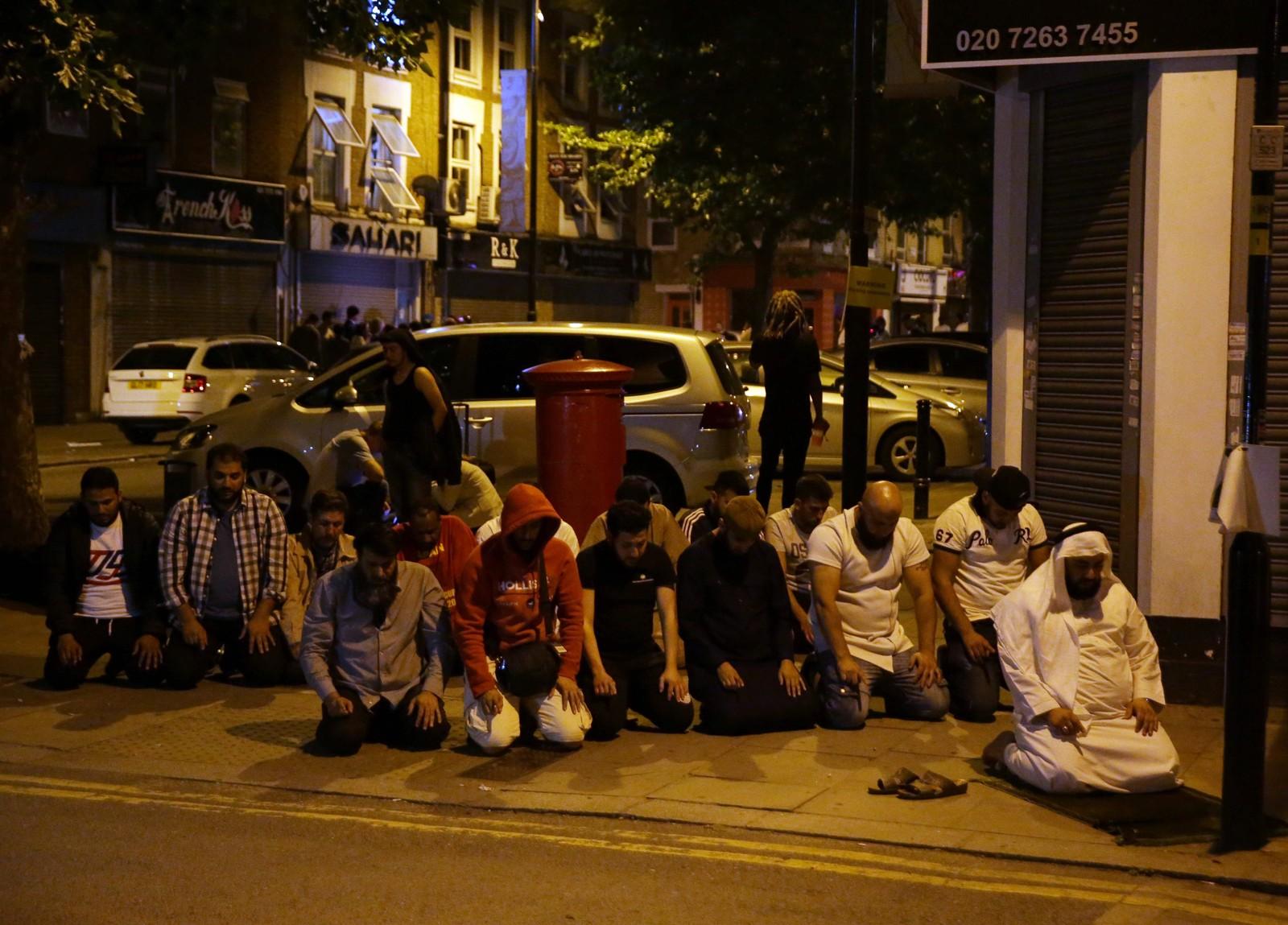 Noen muslimer ba en felles bønn på gata etter angrepet.