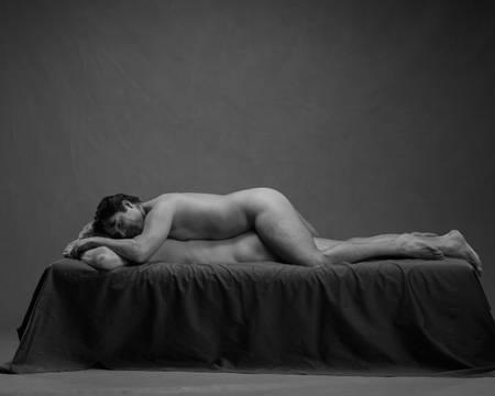 En naken mann ligger flatt på magen på senga. En annen naken mann ligger oppå ham