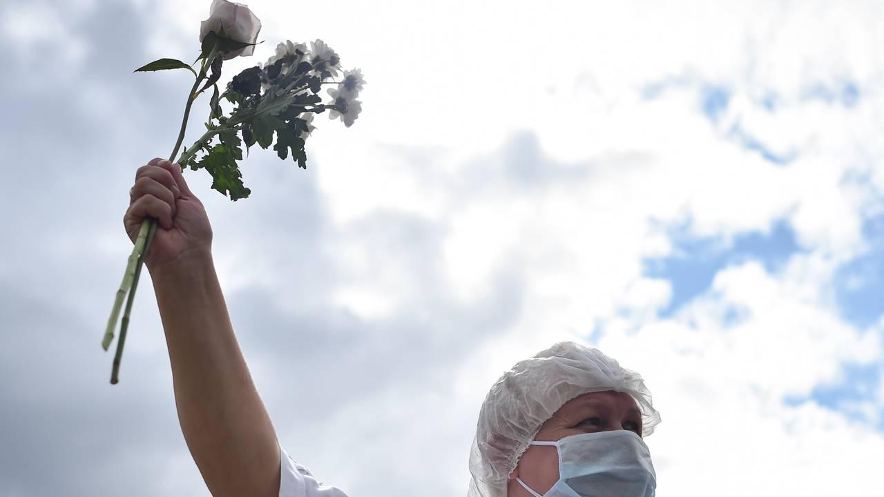 En sykehusarbeider demonstrerer med blomster i Minsk, Hviterussland.