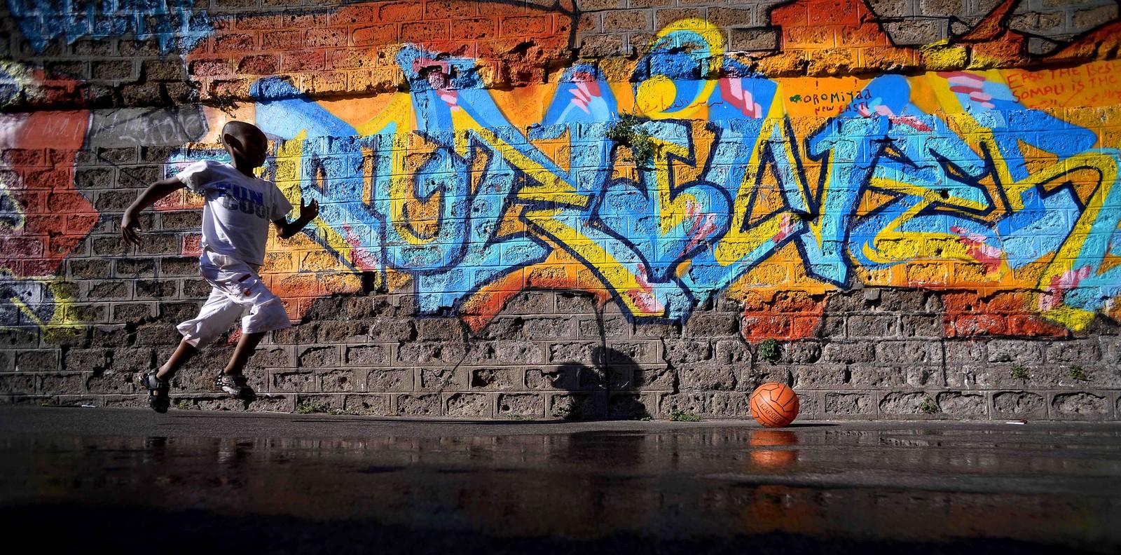 En ung flyktning løper etter en ball i gaten Via Cupa utenfor det tidligere flyktningmottaket Baobab i Roma i Italia den 8. august. Flyktningmottaket ble lagt ned i desember 2015 etter terrorangrepene i Paris, men frivillige fikk raskt satt opp en leir på gaten foran mottaket med telt og toaletter. Det blir også servert tre måltider hver dag.